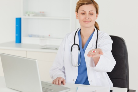 Pretty female doctor showing pills to the camera while sitting in her office photo