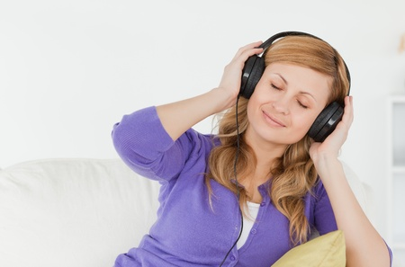 living moment: Beautiful red-haired woman listening to music and enjoying the moment while sitting on a sofa in the living room