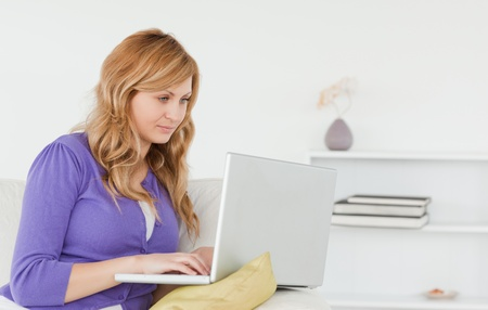 Beautiful red-haired woman sitting on the sofa and using a laptop in her appartment photo