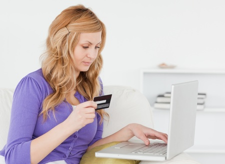Careful woman sitting on a sofa is going to make a payment on the internet in her appartment Stock Photo - 10191560