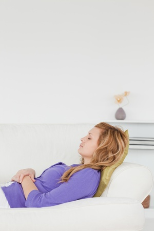 Beautiful woman taking a rest lying on her back on a sofa in the living room photo