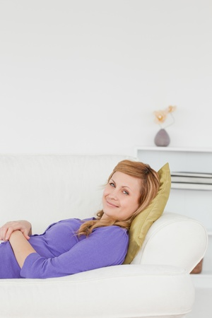 Beautiful woman taking a rest and posing while lying on a sofa photo