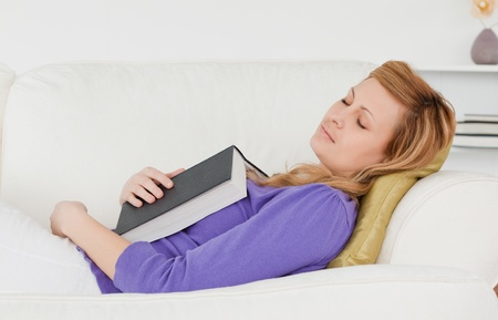 Beautiful woman lying on the sofa who has fallen asleep while reading a book photo