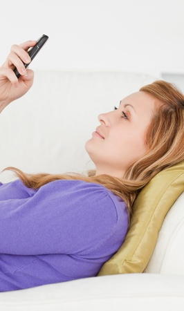 Profile portrait of a good looking woman writing a text message while lying on a sofa in the living room photo