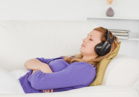 Good looking red-haired woman listening to music while taking a rest lying on a sofa in the living room photo
