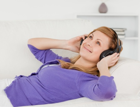 Beautiful red-haired woman listening to music and enjoying the moment while lying on a sofa in the living room photo