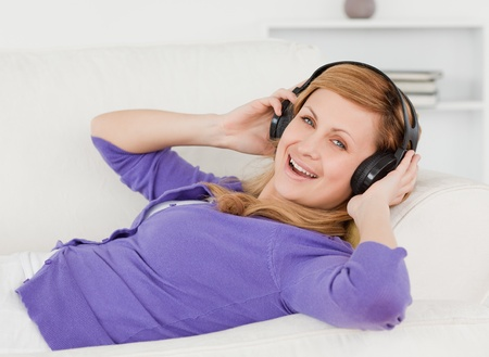 liying: Joyful red-haired woman listening to music and enjoying the moment while lying on a sofa in the living room