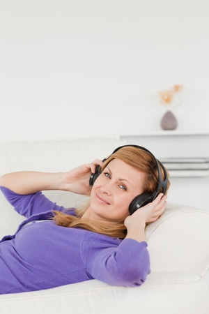 Smiling red-haired woman listening to music and enjoying the moment while lying on a sofa in the living room Stock Photo - 10198721
