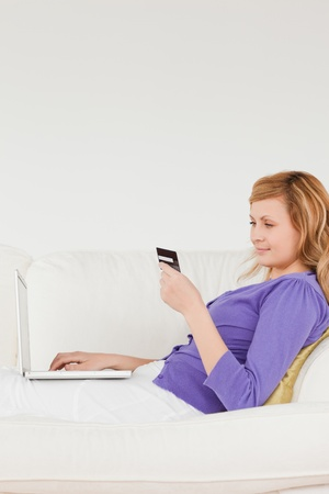 Good looking red-haired woman using a laptop and phone while lying on a sofa in a studio Stock Photo - 10197836