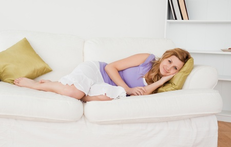 Beautiful woman taking a rest and posing while lying on a sofa in the living room Stock Photo - 10193166