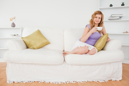 Beautiful red-haired woman holding a cup of coffee and posing while sitting on a sofa in the living room photo