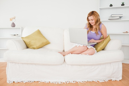 Beautiful red-haired woman sitting on a sofa and using a laptop in a studio photo