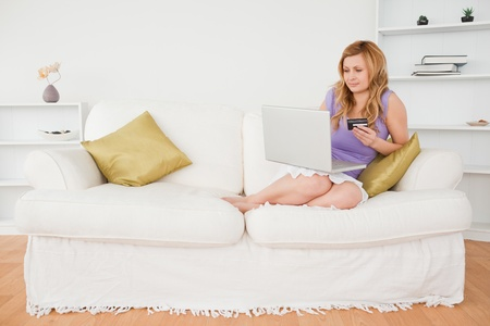 Good looking woman sitting on a sofa is going to make a payment on the internet while sitting on a sofa in the living room photo