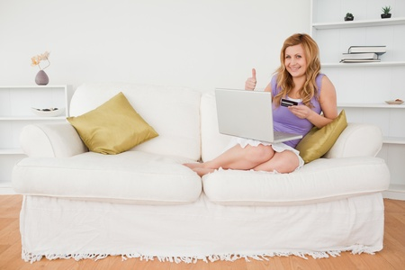 Happy woman sitting on a sofa is going to make a payment on the internet while sitting on a sofa in the living room photo