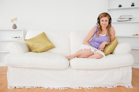 Good looking red-haired woman listening to music and posing while sitting on a sofa in the living room photo