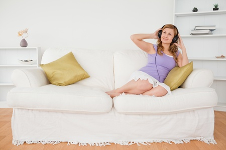 Good looking red-haired woman listening to music and enjoying the moment while sitting on a sofa in the living room photo