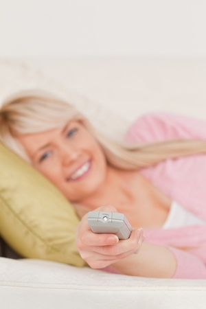 Beautiful blonde woman posing while lying on a sofa in the living room Stock Photo - 10197741