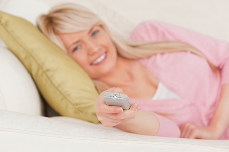Gorgeous blonde female posing while lying on a sofa in the living room photo