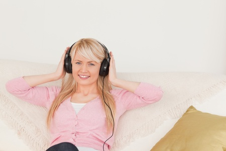 Good looking female listening to music on her headphones while sitting on a sofa in the living room photo