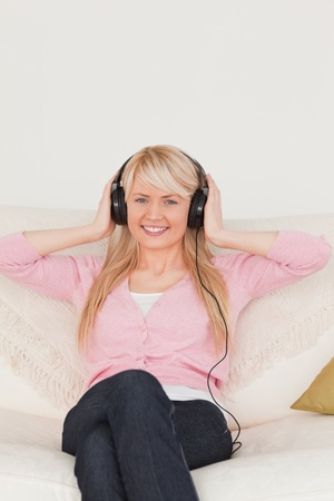 Attractive woman listening to music on her headphones while sitting on a sofa in the living room photo