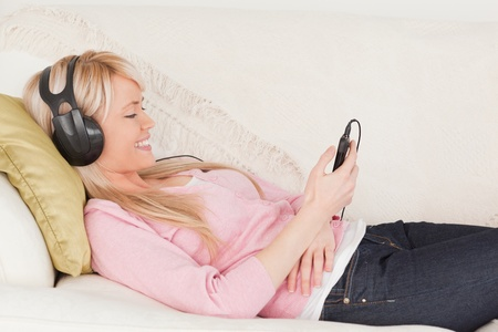 Beautiful woman listening to music on her headphones while lying on a sofa in the living room photo