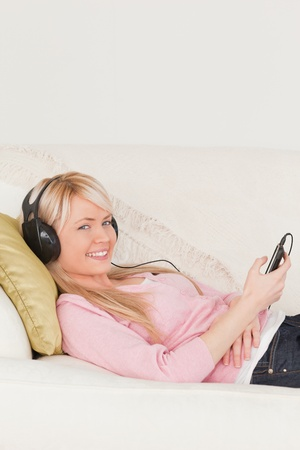 Beautiful female listening to music on her headphones while lying on a sofa in the living room photo