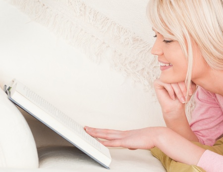 Young beautiful female reading while lying on a sofa in her living room Stock Photo - 10194283