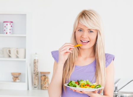 Smiling woman eating her salad in the kitchen photo