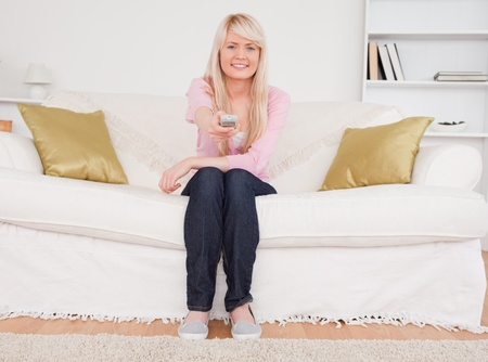 Beautiful blonde female posing while sitting on a sofa in the living room photo