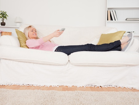 Pretty blonde woman watching tv while lying on a sofa in the living room photo