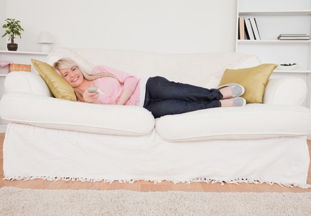 Attractive blonde woman watching tv while lying on a sofa in the living room photo