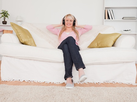 Beautiful blonde female listening to music on her headphones while sitting on a sofa in the living room photo