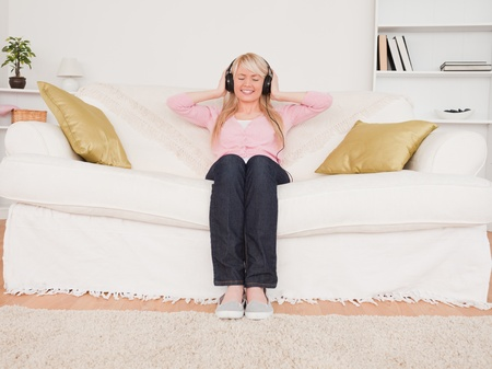 Beautiful blonde woman listening to music on her headphones while sitting on a sofa in the living room photo