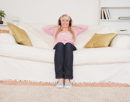 Attractive blonde female listening to music on her headphones while sitting on a sofa in the living room photo