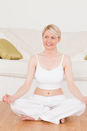 Young woman doing yoga in the living room in her appartement photo