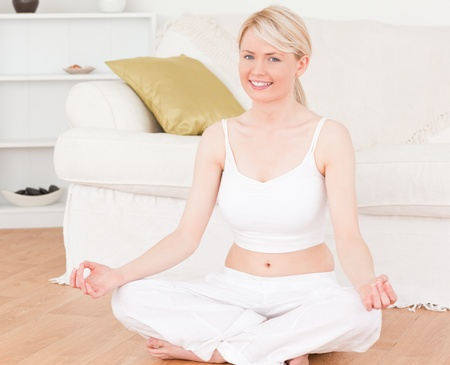 Young female doing yoga in the living room in her appartement photo