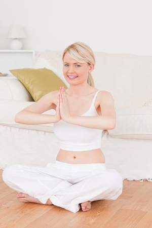 Young blonde female doing yoga in the living room in her appartement Stock Photo - 10198926