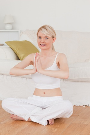 Young good looking woman doing yoga in the living room in her appartement photo