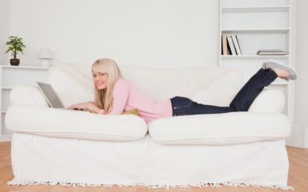 Young blonde woman posing with her laptop while lying on a sofa in her living room photo