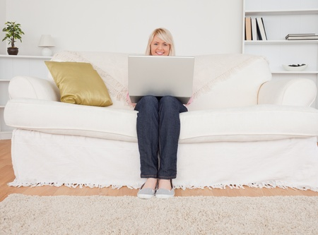 Young blonde woman relaxing with a laptop while sitting on a sofa in her living room photo
