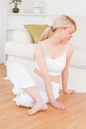 Young blonde female doing relaxation exercises while sitting on the floor in the living room photo