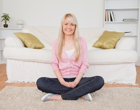 Beautiful blonde female posing while sitting on the floor in the living room Stock Photo - 10206057