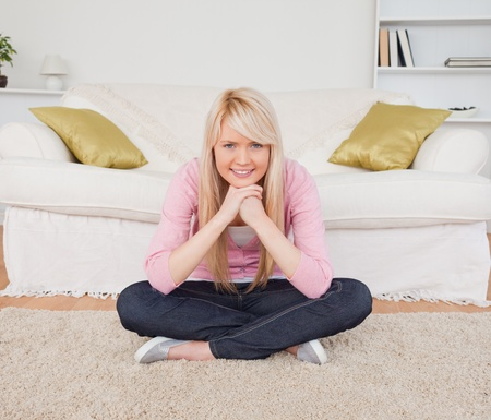 Beautiful blonde woman posing while sitting on the floor in the living room photo