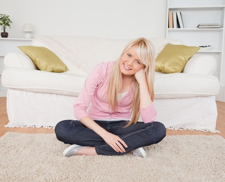 Attractive blonde female posing while sitting on the floor in the living room Stock Photo - 10206159