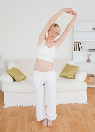 Beautiful blonde female stretching in the living room in her appartment  photo