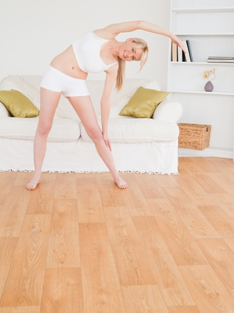 Pretty blonde female stretching in the living room in her appartment  photo