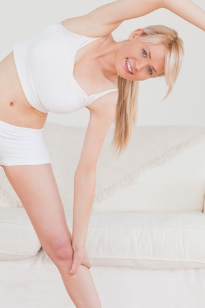Attractive blonde woman posing while stretching in the living room in her appartment  photo