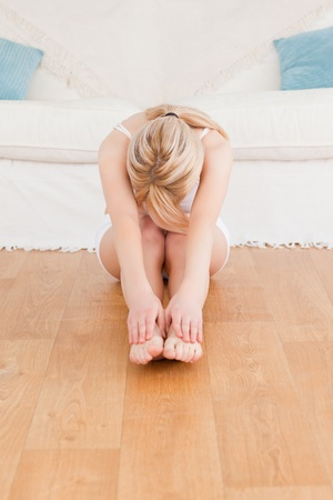 Beautiful woman doing stretching while sitting on the floor in the living rom photo