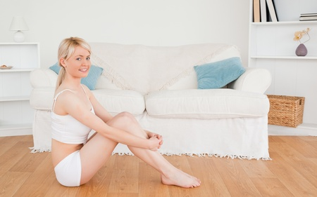 Beautiful female in underwear posing while sitting on the floor in the living rom photo
