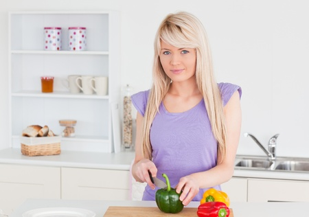 Smiling blonde female cutting vegetables in modern kitchen interior in her appartment photo